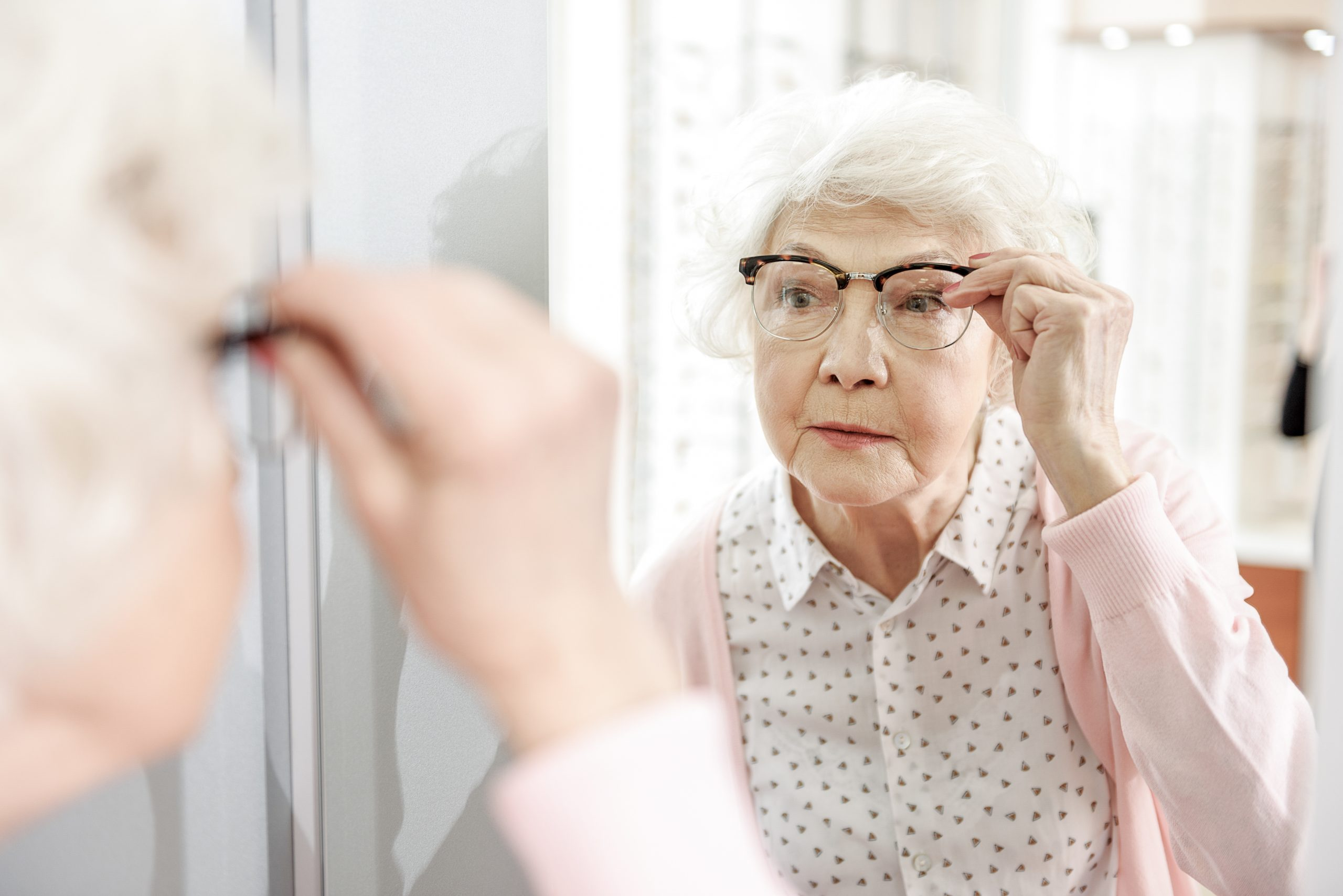 starsza kobieta przymierzająca okulary w salonie optycznym